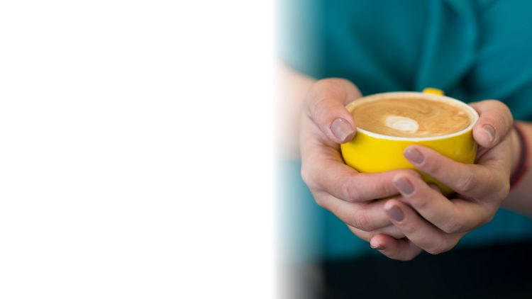 A frothy cup of coffee held in two hands