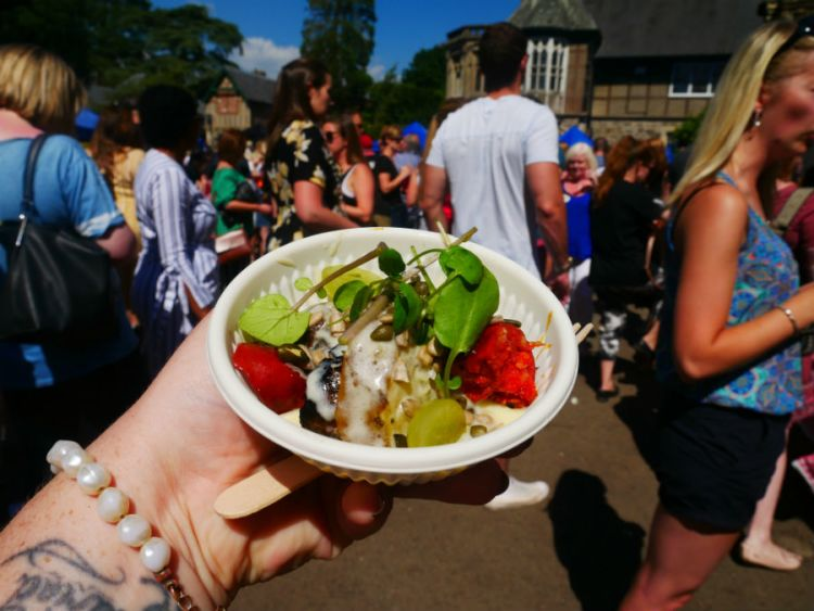 Taken from her perspective, Kacie holds up a bowl of street food at a busy festival
