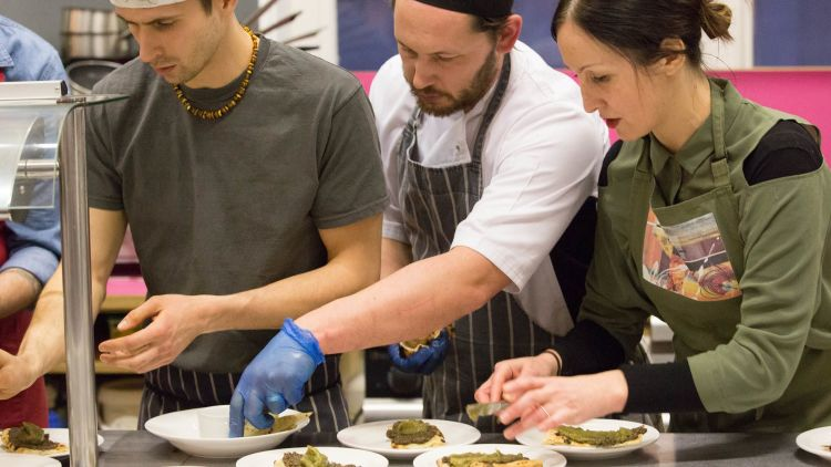 Three chefs are putting the finishing touches to several plates of food