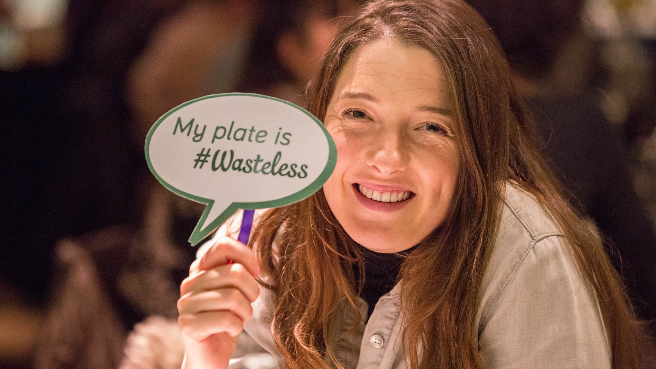 A diner holds up a paper speech bubble reading: My plate is #Wasteless