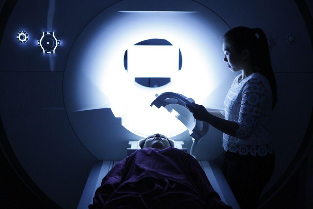 Mae gwyddonydd yn paratoi claf benywaidd ar gyfer sgan MRI
