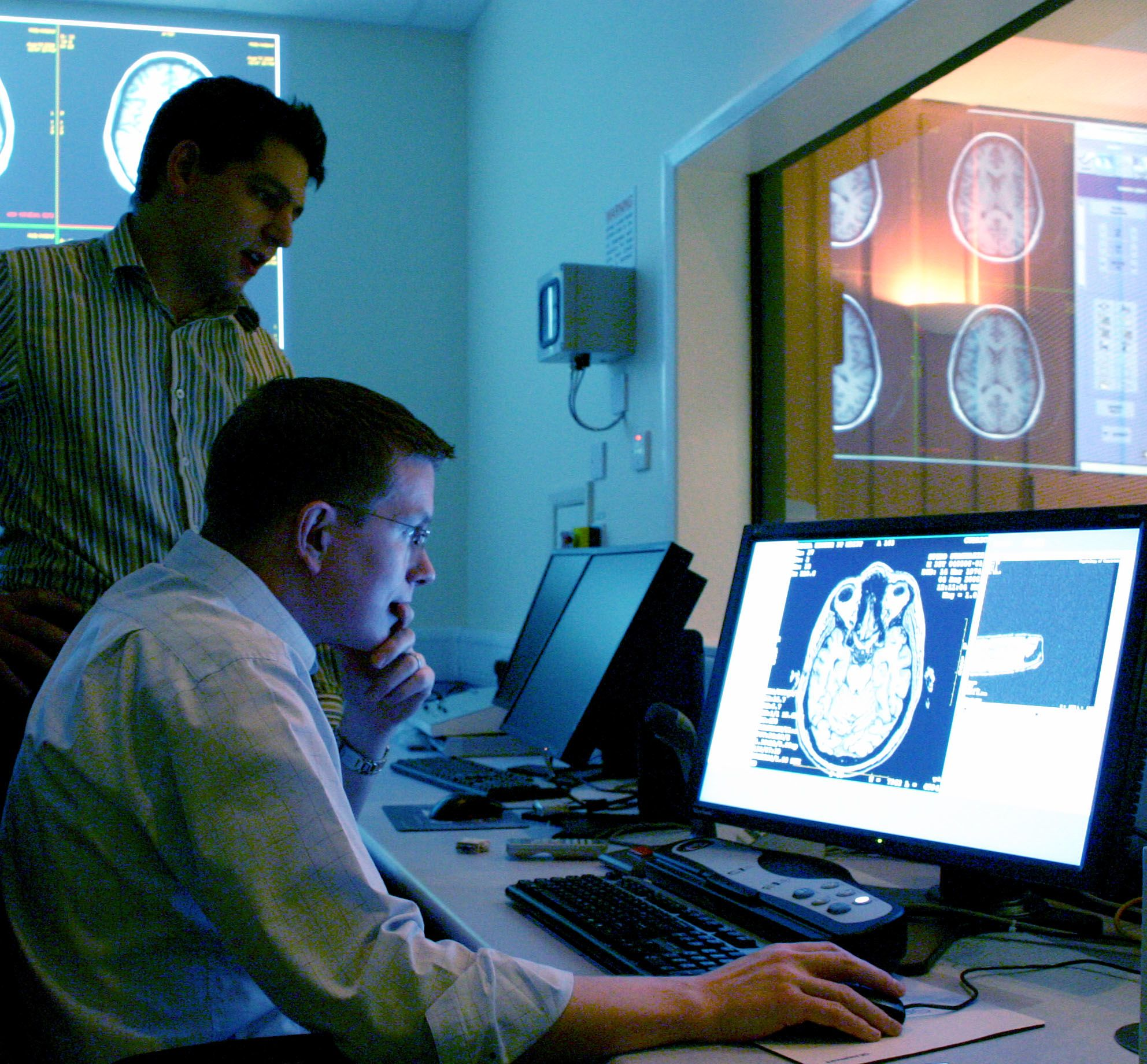 Derek Jones assesses a brain image on a computer screen as a colleague looks over his shoulder