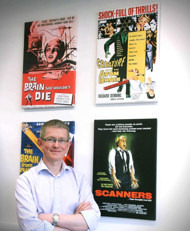 Derek Jones poses in front of scifi film posters in his office.