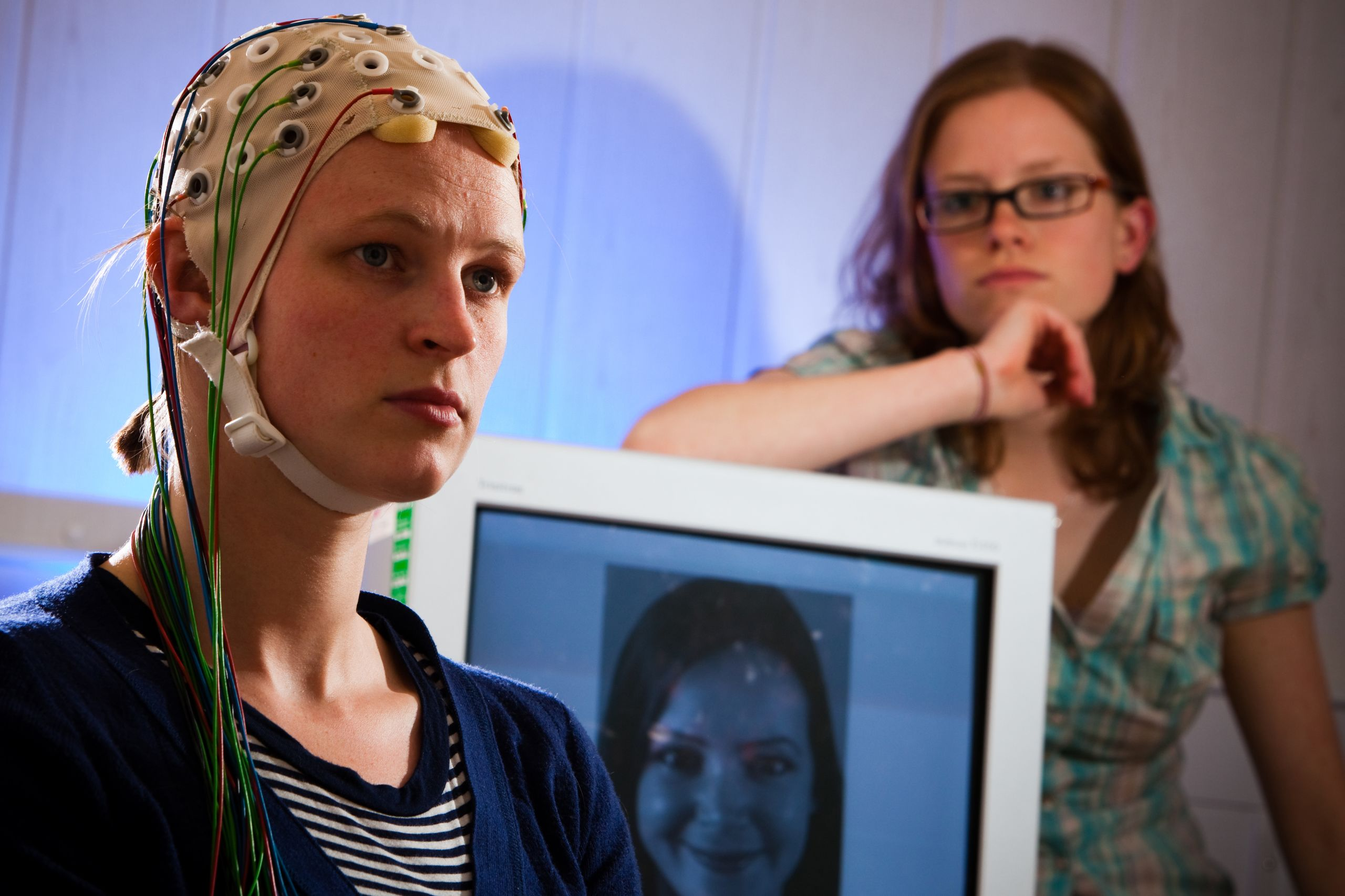 A female volunteer wears a headset with several wires attached as a scientist watches from behind a screen