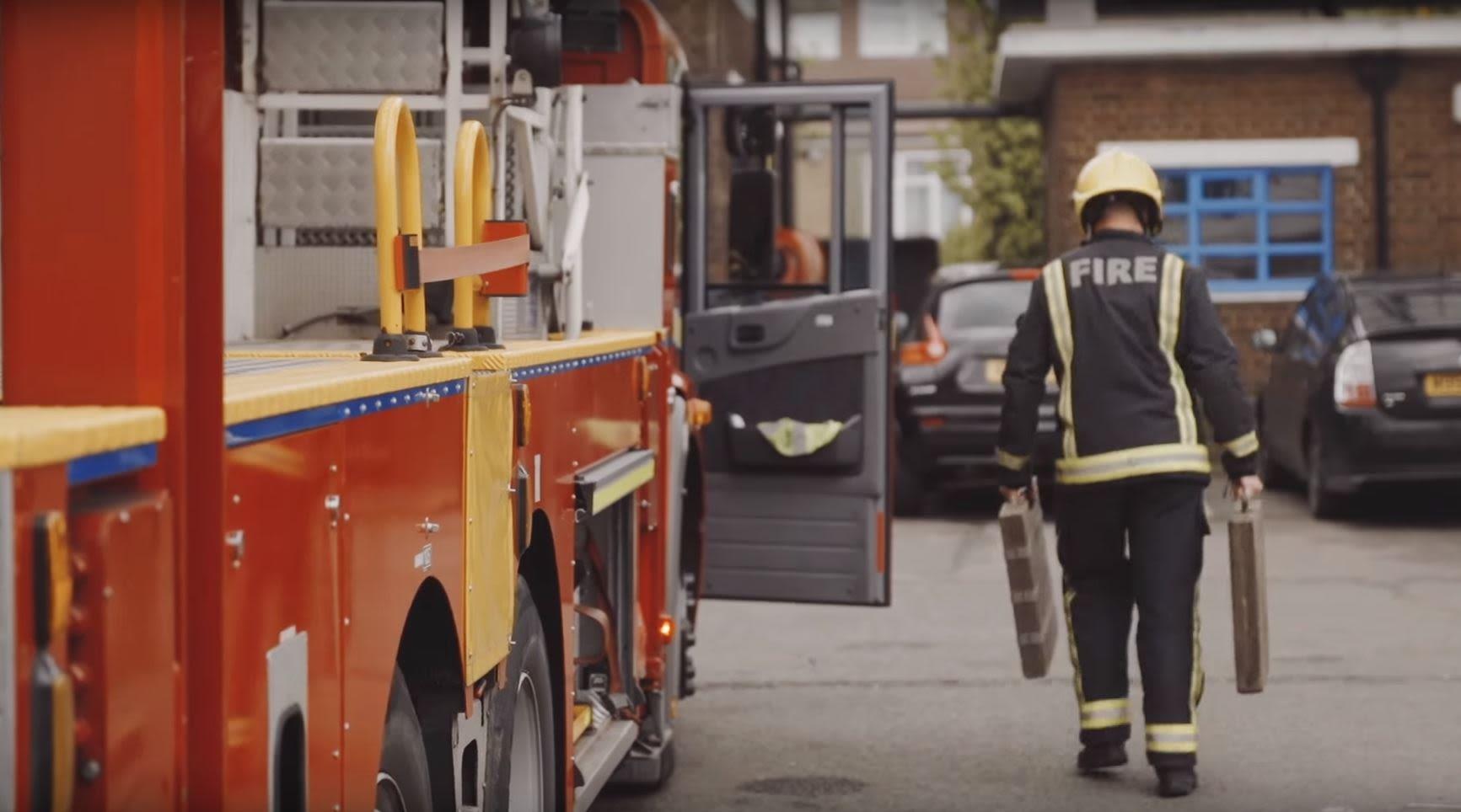 Firefighter alongside fire engine