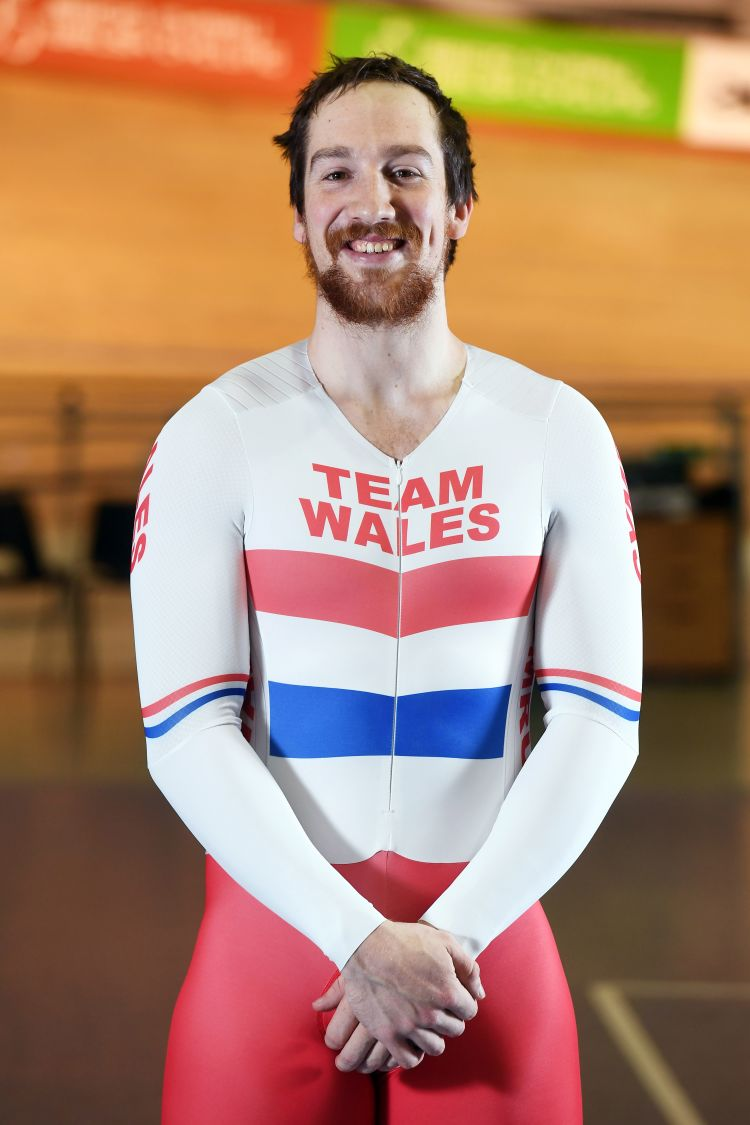 Photograph of Lewis Oliva standing in his Team Wales kit at the Newport Velodrome.